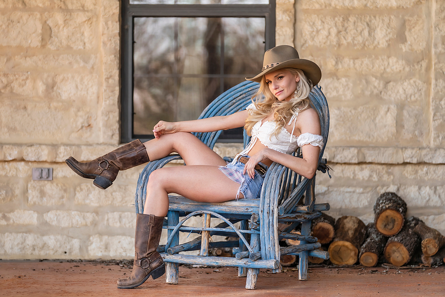 A gorgeous blonde model dressed as a cowgirl enjoying the outdoo